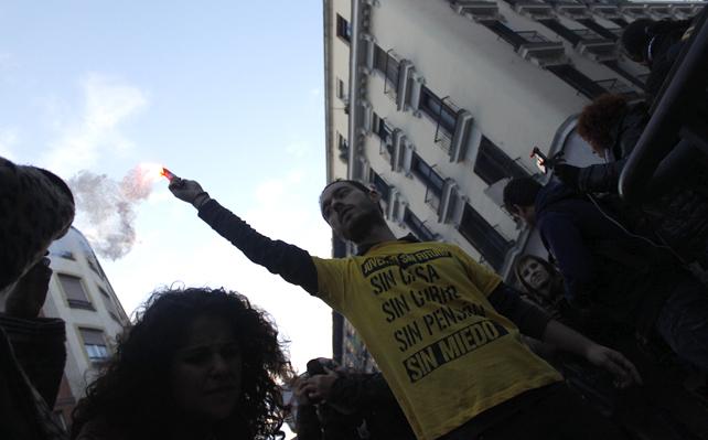 Un manifestante enciende su bengala en la manfiestación de Madrid.