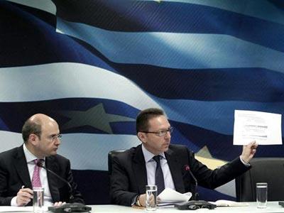 El ministro griego de Finanzas, Yannis Stournaras (d), muestra un papel a los periodistas durante una rueda de prensa ofrecida junto al ministro griego de Desarrollo, Kostis Hatzidakis (i), en el Ministerio de Finanzas de Atenas. -EFE