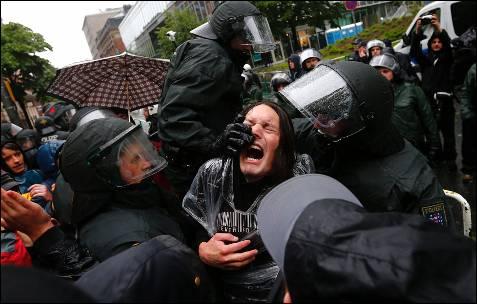 Los policías tratan de reducir a uno de los manifestantes concentrados delante de la sede del BCE.