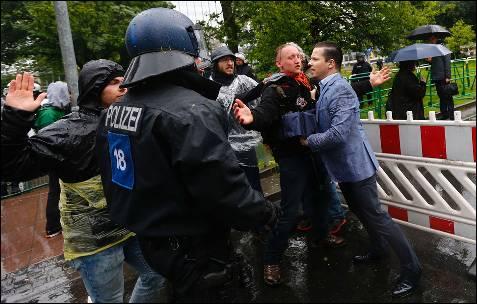 Un empleado que trabaja en el distrito financiero de Fráncfort se enfrenta a algunos de los manifestantes concentrados delante de la sede del BCE.