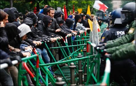 Los manifestantes tratan de levantar la barrera colocada por la policía alemana en torno a la sede del BCE en Fráncfort.
