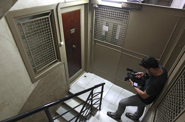 Un periodista toma imágenes del rellano del piso en el que vivía un hombre que iba a ser desahuciado y cuyo cadáver ha sido hallado este lunes por la comitiva judicial que iba a llevar a cabo la orden de desahucio.