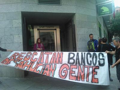 Activistas de Madrid despliegan una pancarta frente a la puetrta de la ofina de Bankia de la calle Pez.