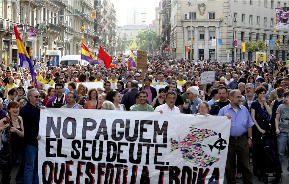 Manifestantes sostienen una pancarta durante la manifestación contra la troika de este primero de junio en las calles de Barcelona. EFE/TONI GARRIGA