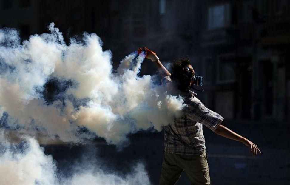 Un manifestante lanza un bote de gas lacrimógeno durante un enfrentamiento contra la policía antidisturbios en la Plaza Taksim de Estambul.