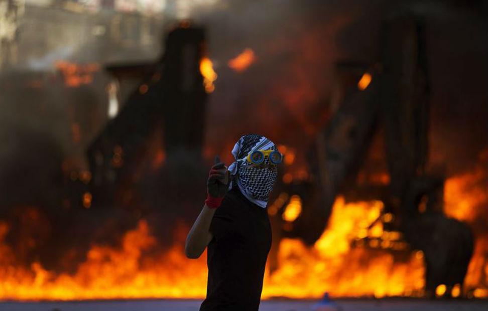 Un manifestante pasa delante de un vehículo incendiado durante un enfrentamiento contra la policía antidisturbios en la Plaza Taksim de Estambul.