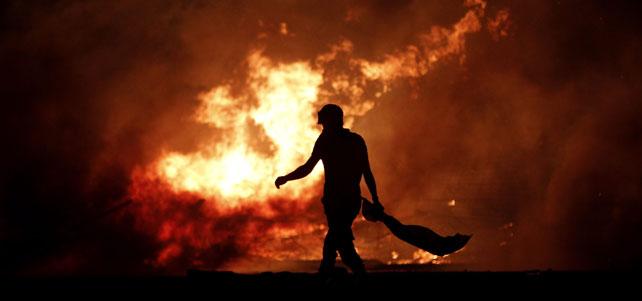 - Un manifestante pasa frente a una barricada en llamas.
