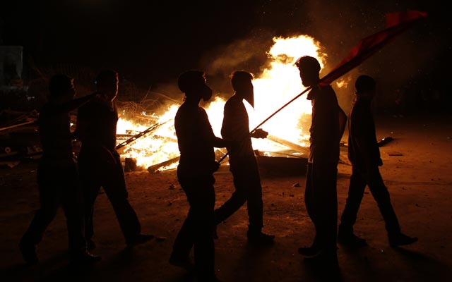 Un grupo de manifestantes camina junto a los restos de una barricada en llamas, durante una nueva noche de enfrentamientos (12 junio)- REUTERS/Murad Sezer