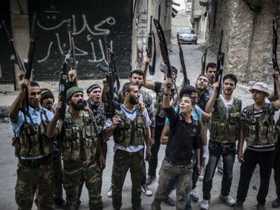 Rebeldes sirios levantan sus armas frente a un edificio destruido. -EFE