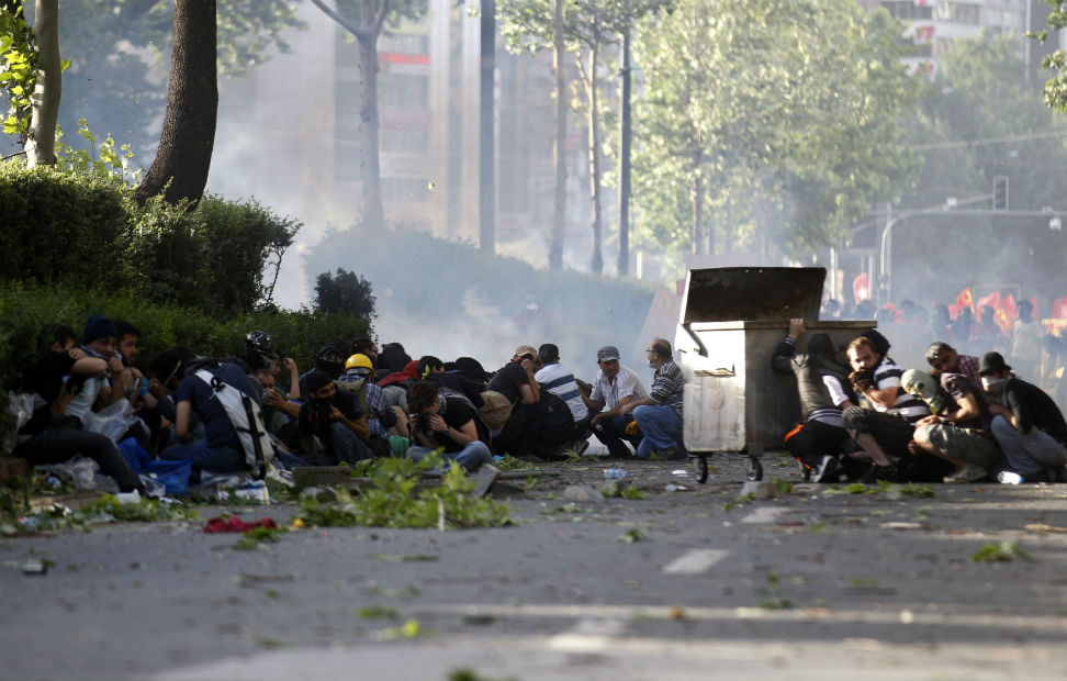 Manifestantes se refugian de los gases lacrimógenos lanzados por la policía turca para reprimir las protestas contra Erdogan.