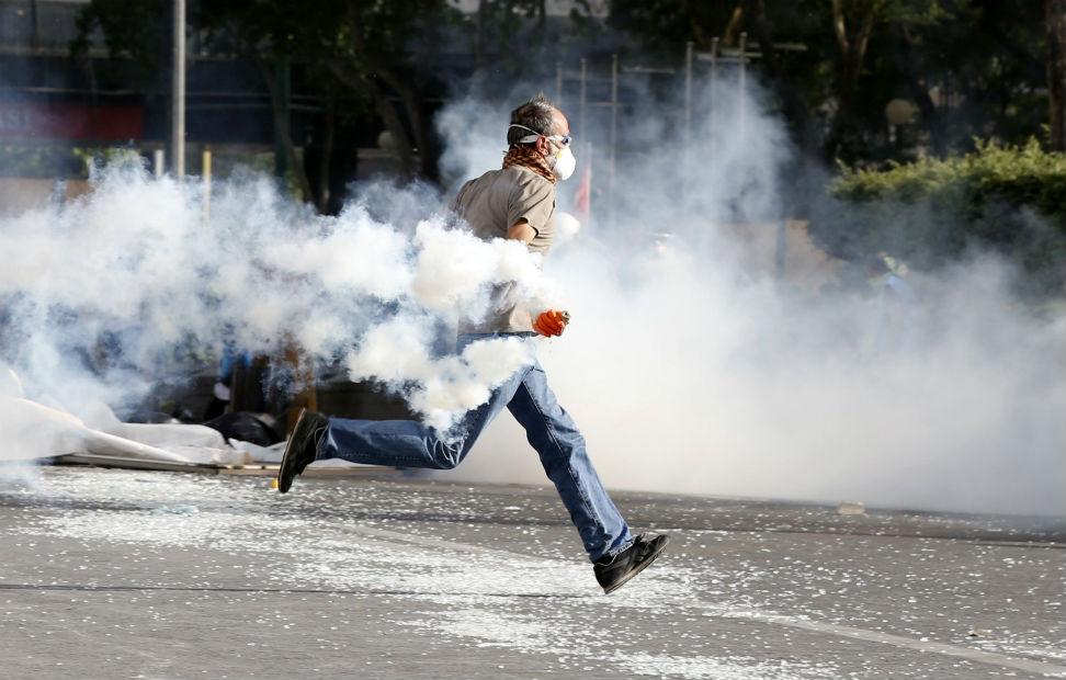 Un indignado turco corre para escapar de una lata de gas lacrimógeno.