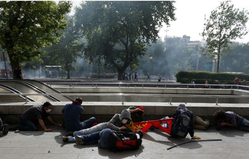 Indignados turcos se refugian del ataque de los antidisturbios, que usan gases lacrimógenos para disolver la manifestación.