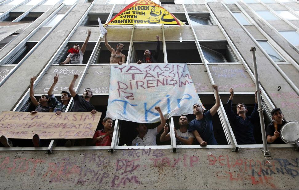 Los indignados turcos gritan consignas contra Erdogan desde las ventanas de un edificio en Estambul.