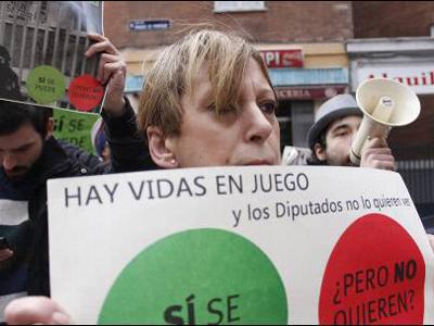 Una mujer protesta por la ILP de la PAH durante el escrache a Soraya Saénz de Santamaría.