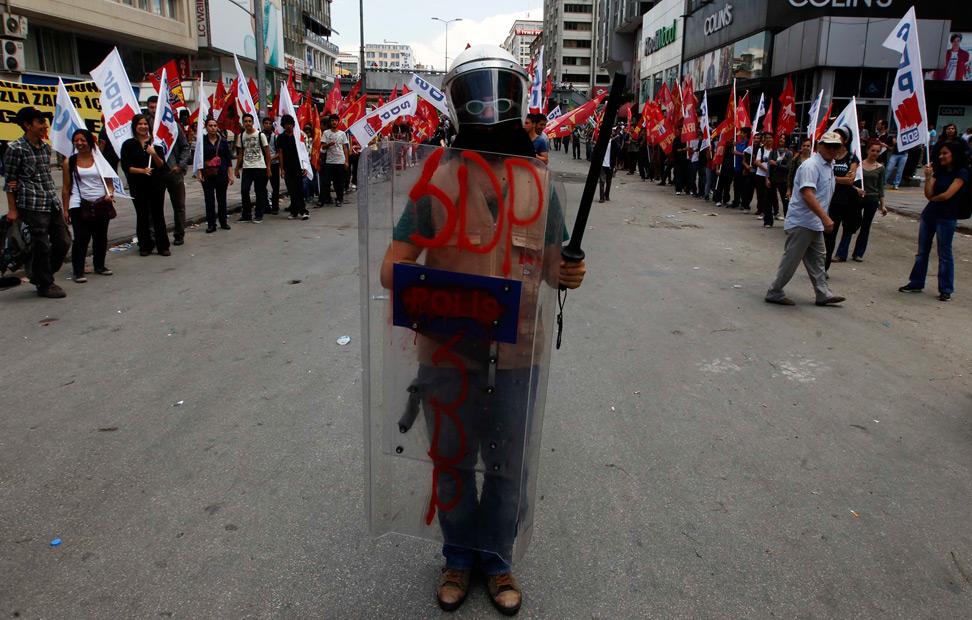 Un manifestante, fotografiado con un casco, un escudo y una porra de policía antidisturbios, en Ankara.