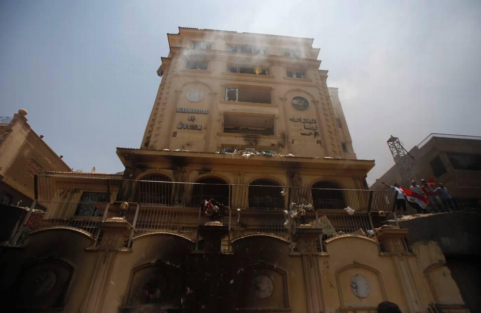 Manifestantes anti-Mursi ondean la bandera egipcia en la incendiada sede de los Hermanos Musulmanes mientras protestan contra el presidente. REUTERS/Amr Abdallah Dalsh
