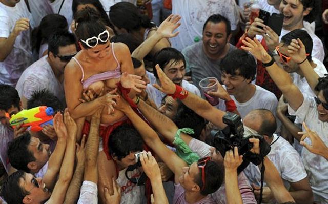 Un joven aúpa a una chica mientras un grupo de hombres trata de manosearla. EFE