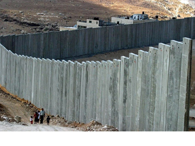 Una familia palestina camina junto a un muro en Cisjordania. EFE