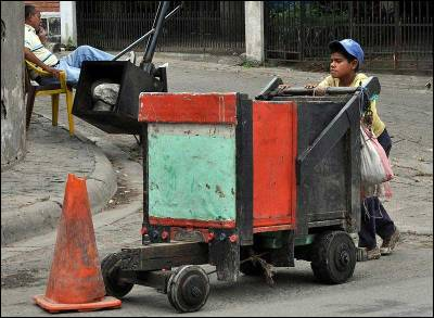 Un niño trabaja con una carreta de madera hoy, domingo 30 de junio de 2013, en un barrio de Tegucigalpa (Honduras).