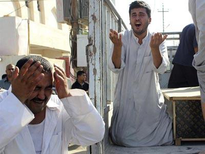 Dos hombres lloran tras ataque a mezquita suní el viernes, que dejó 25 muertos/Efe