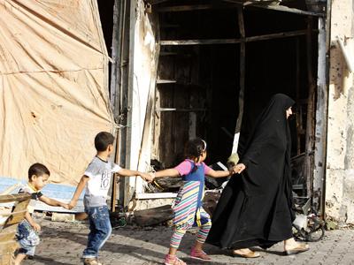 Una familia camina junto al lugar en el que explotó un coche bomba, en el barrio de Tobchi, Bagdad, el 21 de julio de 2013. REUTERS/Thaier al-Sudani