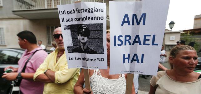 Pancartas contra Erich Priebke: 'El pueblo judío vive' y 'Él puede celebrar su cumpleaños, sus víctimas no'. -REUTERS