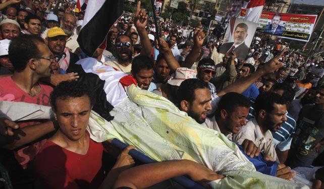 Seguidores del derrocado Mursi llevan el cuerpo de uno de los muertos en los alrededopres de la sede de la Guardia Republicana este lunes.