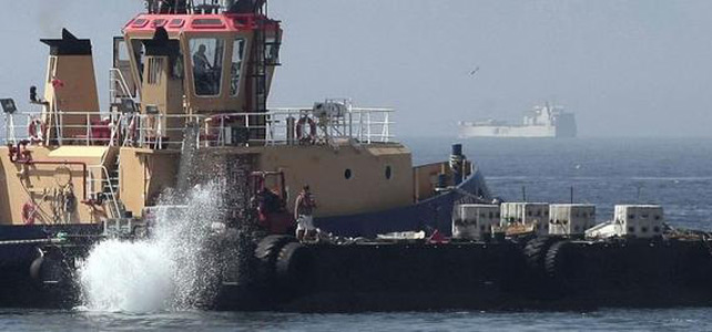 Un remolcador de lanzando al mar bloques de hormigón. -EFE