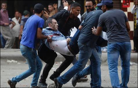 Un grupo de partidarios del depuesto presidente egipcio Mohamed Mursi llevan a uno de los manifestante herido durante los enfrentamientos en la plaza Ramses de El Cairo.
