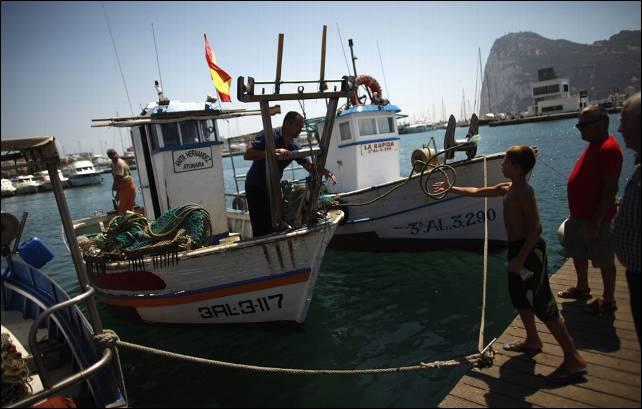 Un pescador español del barco de pesca 'Anita Hernández' lanza una cuerda a un niño después de llegar al Puerto Chico, delante de la Roca de Gibraltar en La Línea de la Concepción.