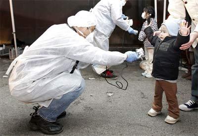 Un técnico mide la radiactividad externa a un niño en las inmediaciones de Fukushima tras el accidente. REUTERS
