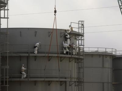 Trabajadores de TEPCO construyen tanques de agua protegidos con trajes y máscaras en la central de Fukushima, en febrero de 2012. REUTERS/Issei Kato