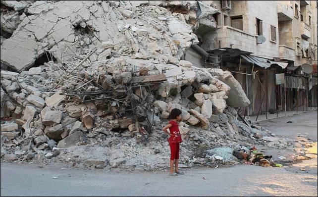 Una niña espera a sus familiares ante las ruinas de un edificio en Idlib tras los bombardeos del régimen.- Reuters