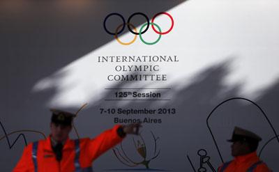 Agentes de seguridad vigilan el hotel Hilton con un cartel que anuncia la 125ª sesión del COI.