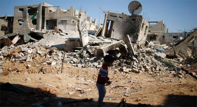Un niño juega junto a las ruinas de la casa de su familia en Gaza.
