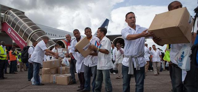 Los primeros miembros de un equipo de 165 médicos cubanos y trabajadores de la salud descargan ellos mismos las cajas de medicamentos y material médico de un avión.