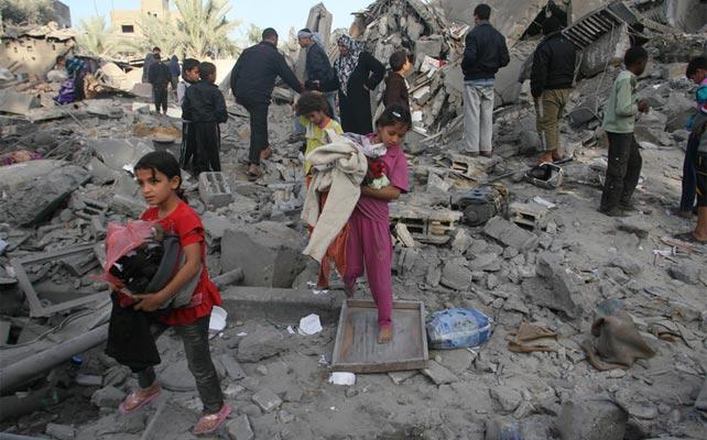 Los niños con sus pertenencias entre los escombros de su casa, en el campo de refugiados de Shabbora, cerca de la ciudad de Rafah, en el sur de la Franja de Gaza.