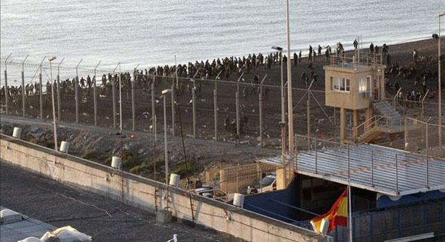 Vista del territorio marroquí desde Ceuta. En el fondo, un grupo de inmigrantes.