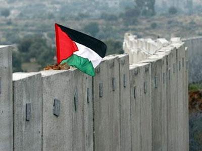 Una bandera ondea sobre el muro de Cisjordania