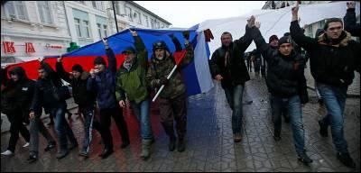 Un grupo de crimeos marchan por Simferópol con una bandera rusa gigante.