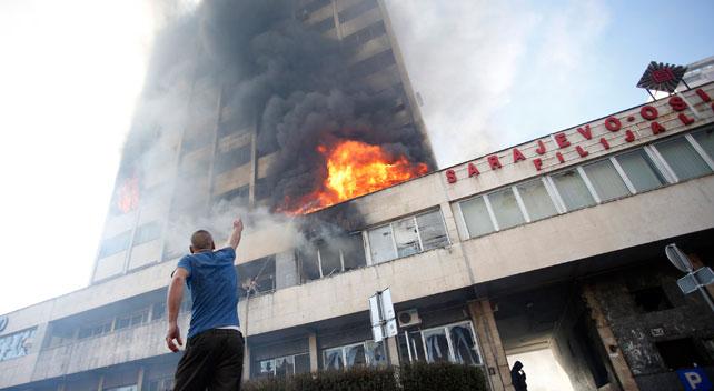 Un manifestante contempla las llamas del interior del edificio de la Presidencia de Bosnia-Herzegovina en Sarajevo.