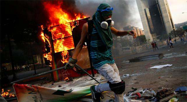 Un manifestante contrario al Gobierno de Maduro junto a un quisco de los trabajadores del metro de Caracas que fue incendiado durante protestas opositoras.