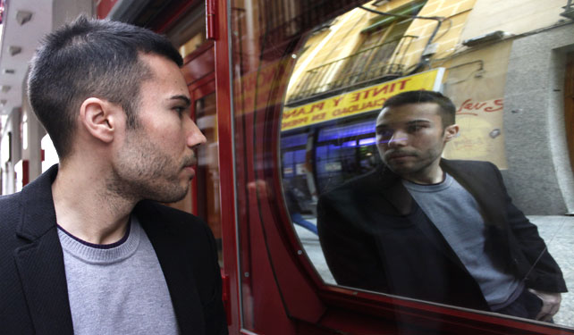El investigador Antoni Aguiló, observa su reflejo en un espejo deformado en el Callejón del Gato de Madrid.