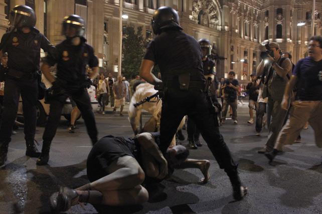 Un manifestante se agarra a la pierna de un antidisturbios durante las cargas policiales tras una manifestación en Madrid