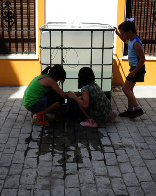 Varias niñas recogen agua de un barril de plástico en las viviendas ocupadas de Bollullos par del Condado, en Huelva. AFP