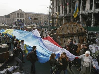Unos ciudadanos ucranianos sostienen una bandera gigante hecha con tres banderas, la de Ucrania, la de Crimea y la de los tártaros de crimea, en la plaza de la Independencia de Kiev, Ucrania.