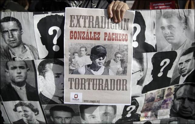 Familiares de víctimas de Franco protestan con una foto del ex inspector de policía Juan Antonio González Pacheco, conocido como 'Billy el niño', y una pancarta con fotografías de las víctimas.