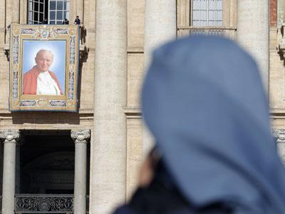 Una monja reza mientras unos trabajadores instalan un tapiz con la imagen del papa Juan Pablo II.- REUTERS