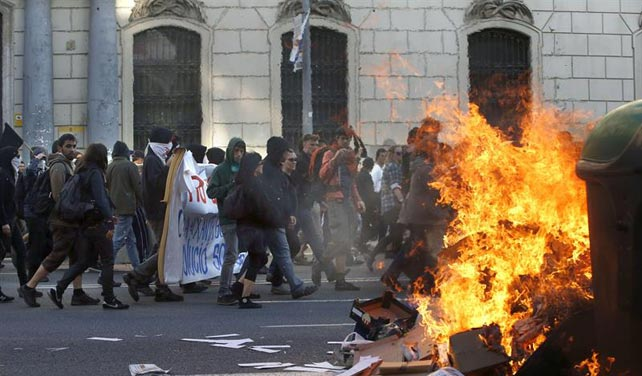 Participantes en una manifestación alternativa convocada esta tarde en Barcelona con motivo del 1 de mayo pasan ante un contenedor ardiendo.