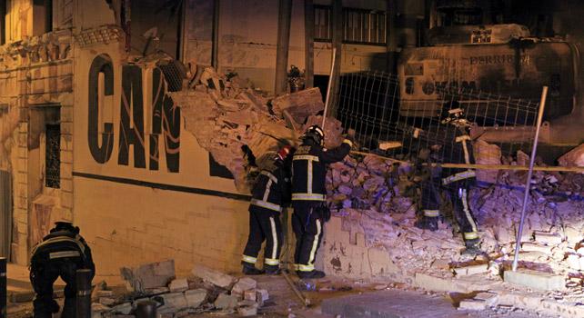 Bomberos trabajan en lo que fue la casa 'okupada' Can Vies tras los disturbios de la pasada noche.